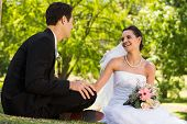 Happy young newlywed couple sitting in the park