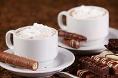 Two Cups Of Coffee Or Hot Cocoa With Chocolates And  Cookies On Brown Background