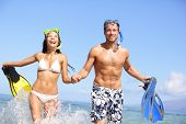 Beach couple having fun in water laughing with snorkeling fins together smiling happy and joyful. Summer holidays travel lifestyle concept under blue sky and sun. Young multiracial couple cheerful.