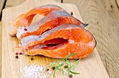 foto of redfish  - Three pieces of trout with rosemary coarse salt and pepper on the background of wooden boards - JPG
