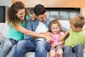 stock photo of tickle  - Cute family tickling little girl on the couch at home in living room - JPG
