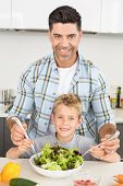Smiling father tossing salad with his cute son at home in kitchen