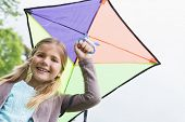 Portrait of a cute young girl with a kite standing outdoors