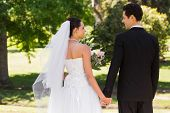 Rear view of a newlywed couple holding hands and walking in the park