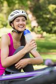 Portrait of a fit young woman in helmet holding water bottle at the park