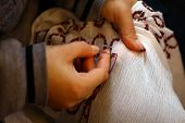 stock photo of thread-making  - Color shot of two hands holding a needle and sewing - JPG