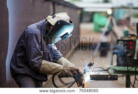 Worker with protective mask welding metal poster