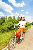 Pretty girl in bicycle helmet rides a bike