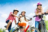 Laughing kids in helmets hold bike handle-bars