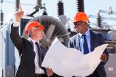 happy managers discussing blueprint at electrical substation
