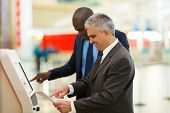 two professional business travellers using self help check in machine at airport