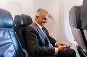happy middle aged businessman using cell phone on airplane