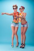 picture of hawaiian girl  - Full length portrait of two beautiful emotional coquette girls with pretty smiles in pinup style with Hawaiian flowers necklaces - JPG