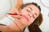 Attractive female patient receiving electro acupuncture on face as part of a anti-aging beauty treat