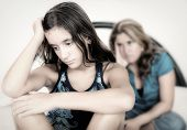 Teenager conflict - Sad teenage girl with her worried mother on the background