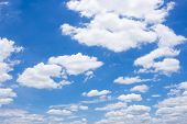 Fluffy White Clouds And Bright Blue Sky.