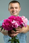 Greetings. Man giving bouquet of flowers. Young beautiful enamored man casual style with flowers.