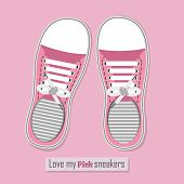 A pair of pink sneakers on pink background