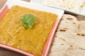 image of tadka  - Tarka Dal - Indian yellow split pea curry garnished with coriander and served with pilau rice and chapatis. Close up.