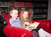 Children reading book at home. Boy and girl in library