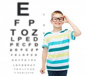 vision, ophthalmology and childhood concept - smiling little boy in eyeglasses over eye chart backgr