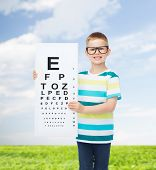 vision, health, ophthalmology, childhood and people concept - smiling little boy wearing eyeglasses with eye chart over natural background