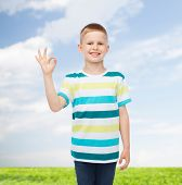 childhood, accomplishment, gesture and people concept - smiling little boy in casual clothes making OK gesture over natural background