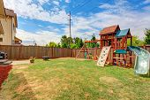 pic of grass area  - Fenced backyard with patio area and playground for kids during sunny summer day - JPG