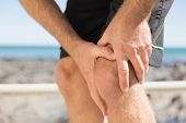 Fit man gripping his injured knee on a sunny day