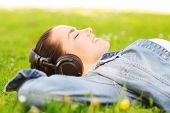 lifestyle, summer vacation, technology, music and people concept - smiling young girl in headphones