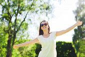 summer, leisure, vacation and people concept - smiling young woman wearing sunglasses standing in pa
