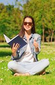 lifestyle, summer vacation, education, gesture and people concept - smiling young girl with book sho