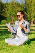 lifestyle, summer vacation, education, drinks and people concept - smiling young girl reading notes
