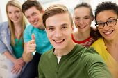 education, leisure and technology concept - five smiling students taking selfie at school