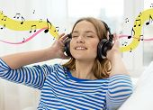 technology, music and happiness concept - smiling young girl in headphones at home