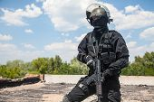 picture of anti-terrorism  - Spec ops soldier in black uniform and face mask with his rifle