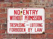 Trespassing Sign Mounted On Brick Wall