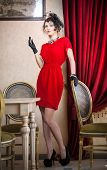 Beautiful woman in red with gloves and creative hairstyle posing near long purple  curtains