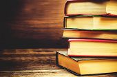 stock photo of education  - stack of books on the dark wood background - JPG