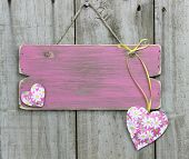 Blank weathered pink sign with flower hearts hanging on wooden door