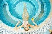 High angle view of young woman resting in swimming pool
