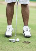 Golf player at the putting green hitting ball