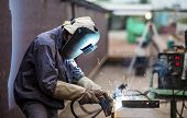 stock photo of smoke  - Worker with protective mask welding metal in factory - JPG