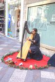 Madrid. Musician In Ancient Clothes Playing The Harp