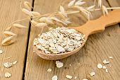 stock photo of oats  - Oat flakes in wooden spoon stalks of oats on the background of wooden boards - JPG