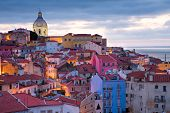stock photo of morning  - View on the old town Alfama in Lisbon Portugal in the very early morning with the street lights still burning - JPG