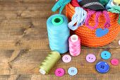 Round orange box full of multicoloured thread and everything necessary for sewing on wooden background