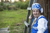 Old woman in ethnic clothes, outdoors. Picture with space for your text.