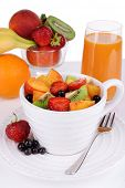 Fresh fruits salad in bowl with berries and juice on light background