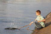 little boy with backpack near pond. he is wallop water. splash.